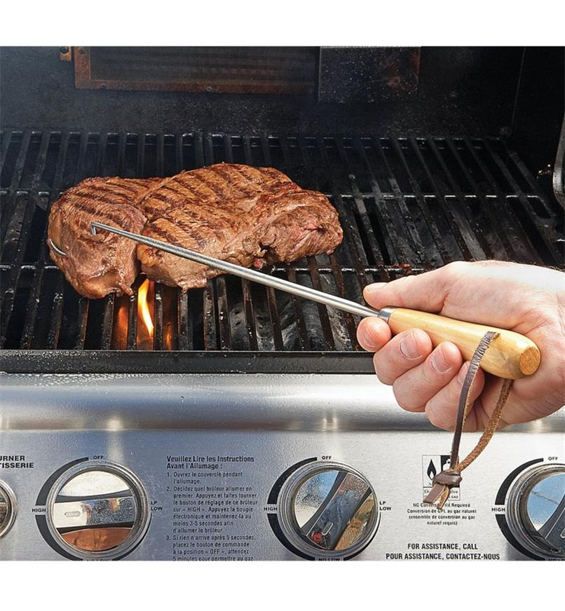 Turning a steak on a barbecue using a Pigtail Flipper
