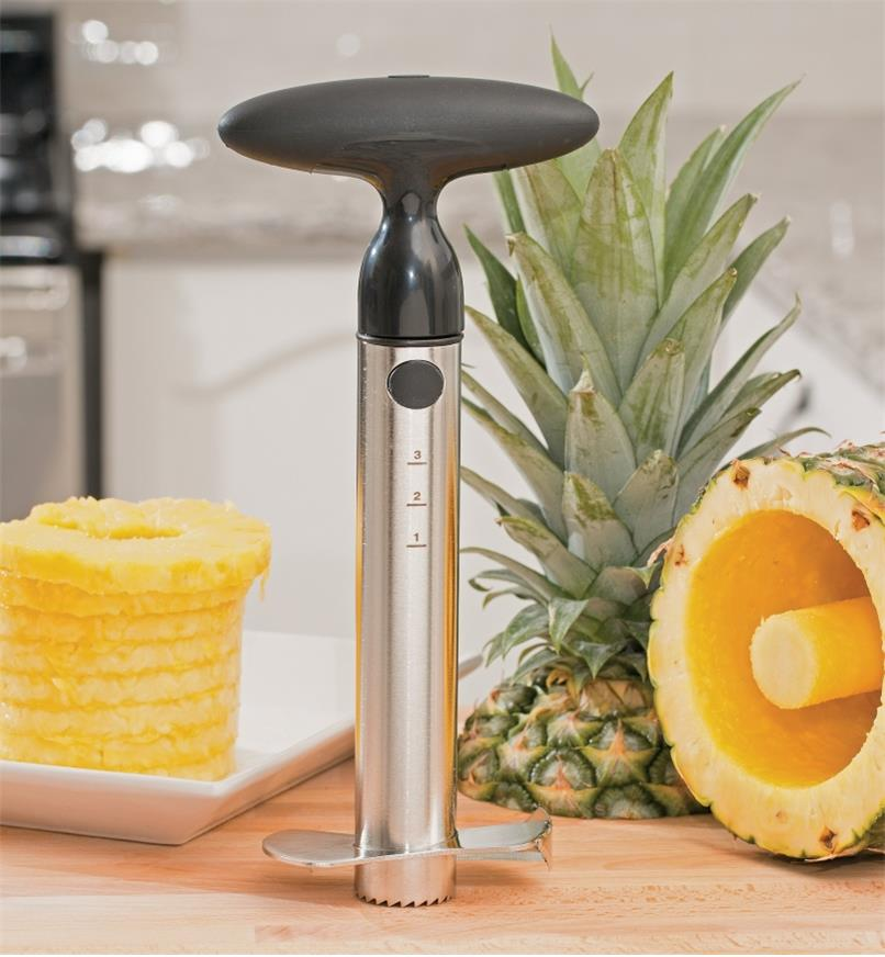 Ratcheting Pineapple Corer & Slicer on a counter beside cored and sliced pineapple