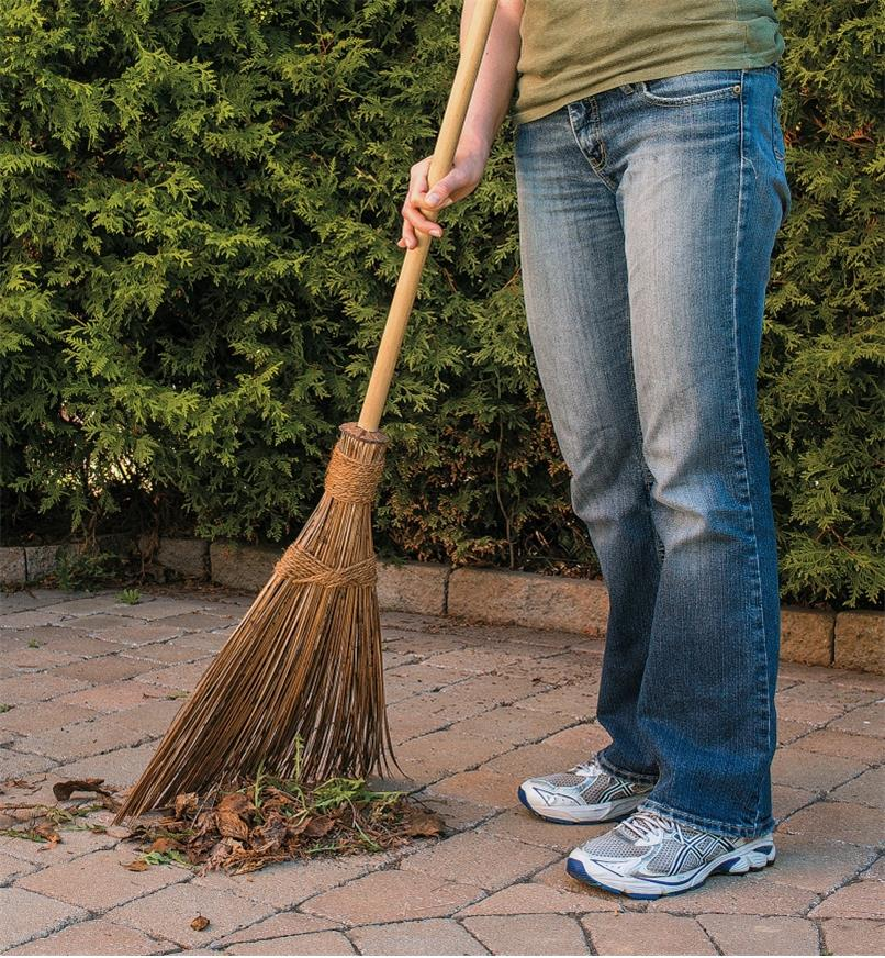 A woman sweeps debris from a patio using an Outdoor Broom