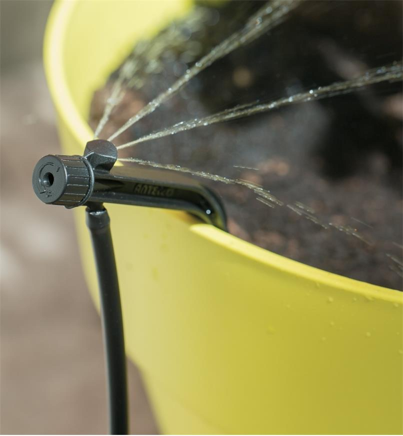 Potstream Emitter attached to the edge of a pot, emitting water