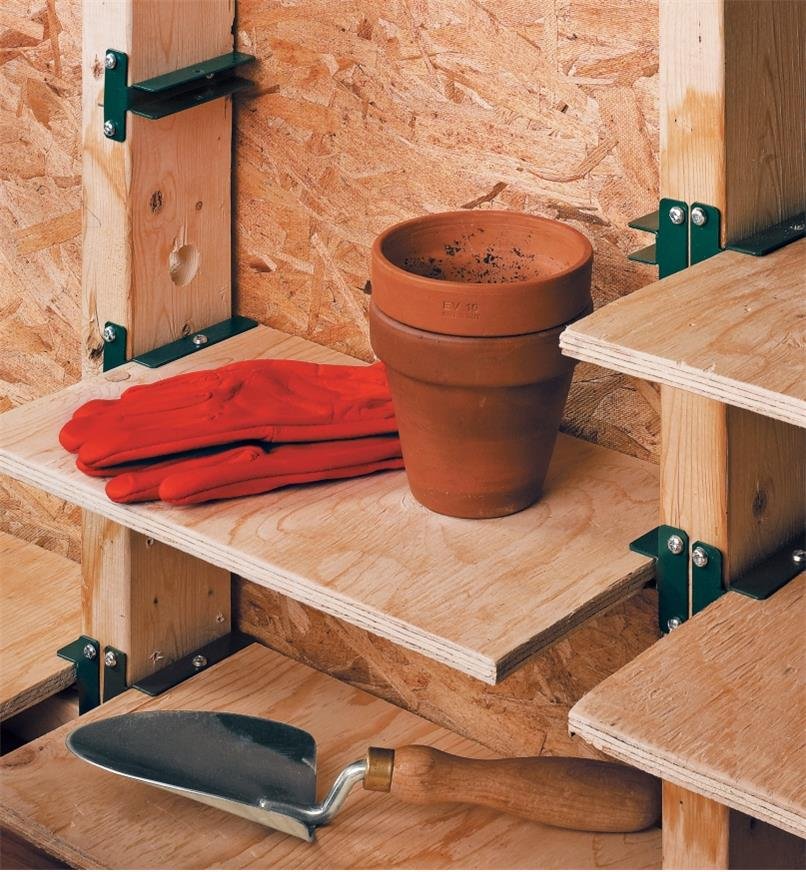 Shelf brackets used to make shelves between wall studs for holding gardening supplies