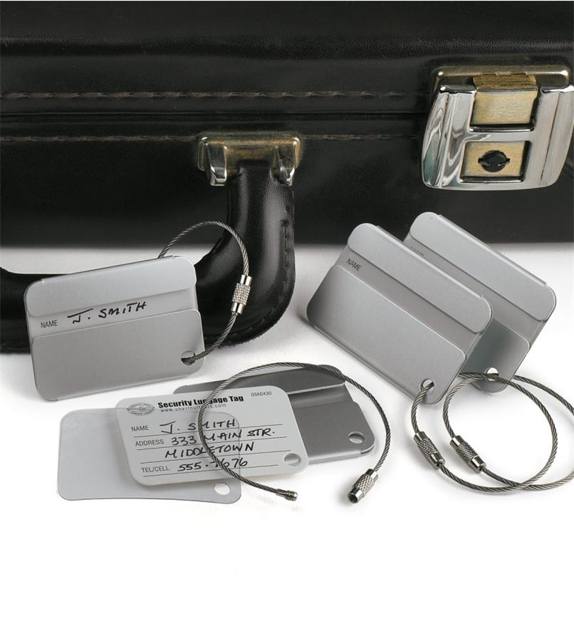 Security-Style Luggage Tag attached to a briefcase handle, with three more tags around it