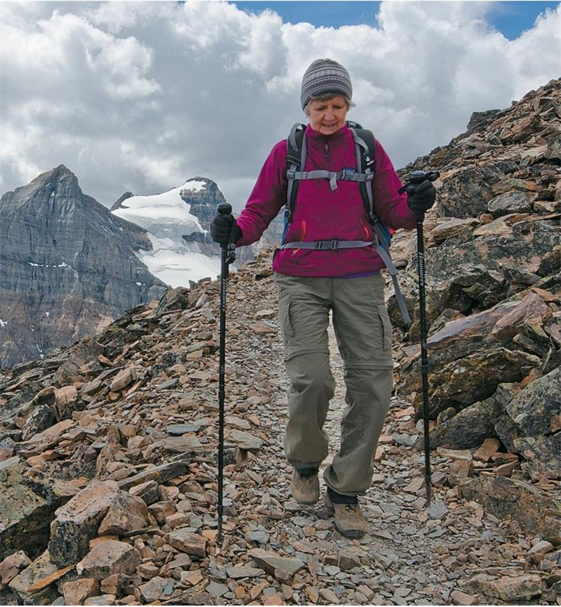 A woman hikes in the mountains with the aid of two telescoping hiking sticks