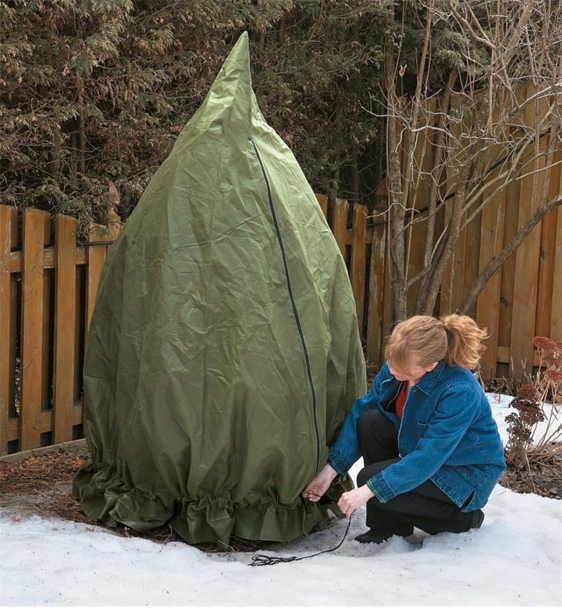 A woman cinches the drawstring of a Shrub & Potted Plant Protector around the bottom of a shrub