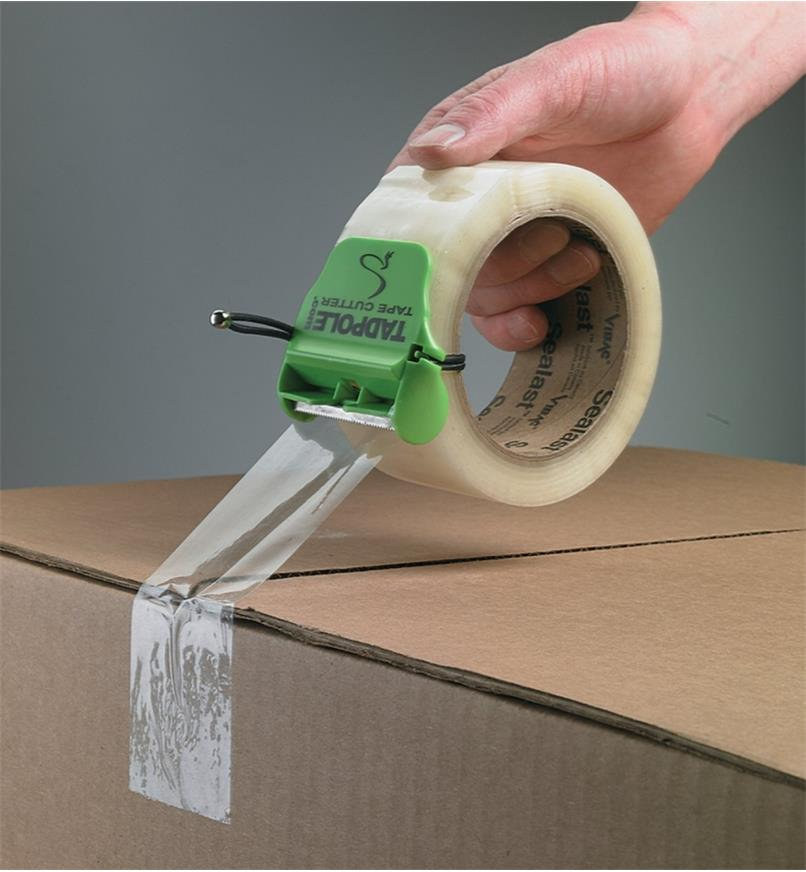 Taping a cardboard box shut using packing tape with the Tadpole Tape Cutter attached