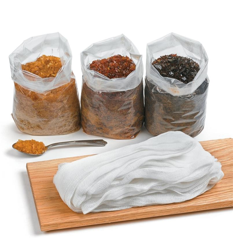 Three bags of shellac behind a wooden board with cheese cloth on top
