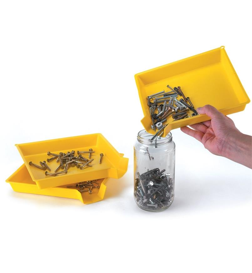 Pouring screws from a sorting tray into a jar