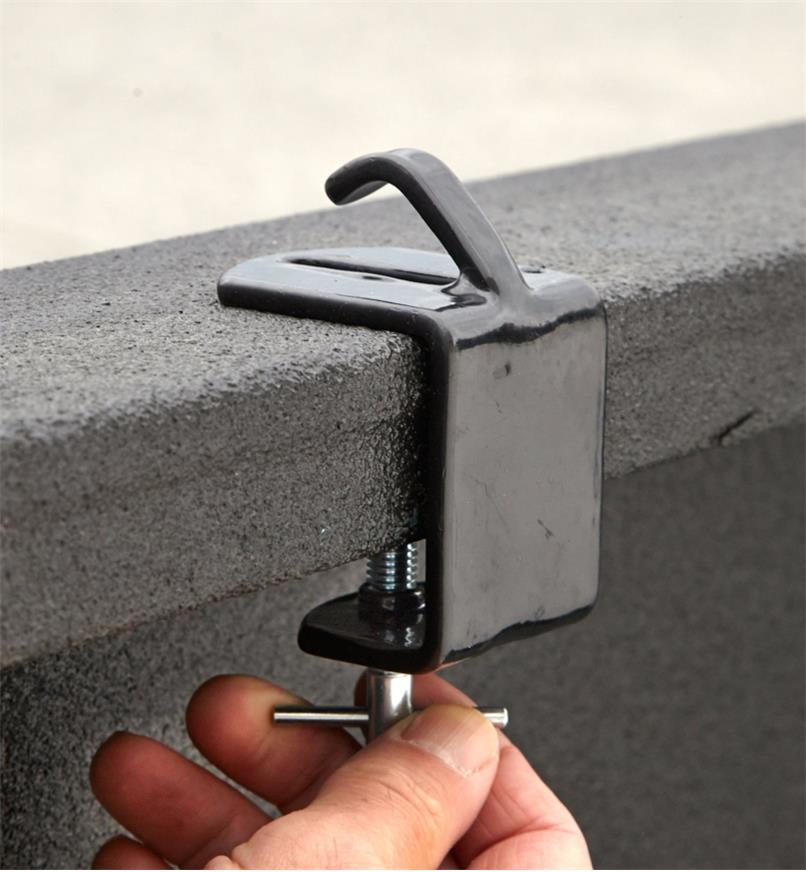 Tightening the clamping screw on a tie-down anchor to secure it to a truck rail