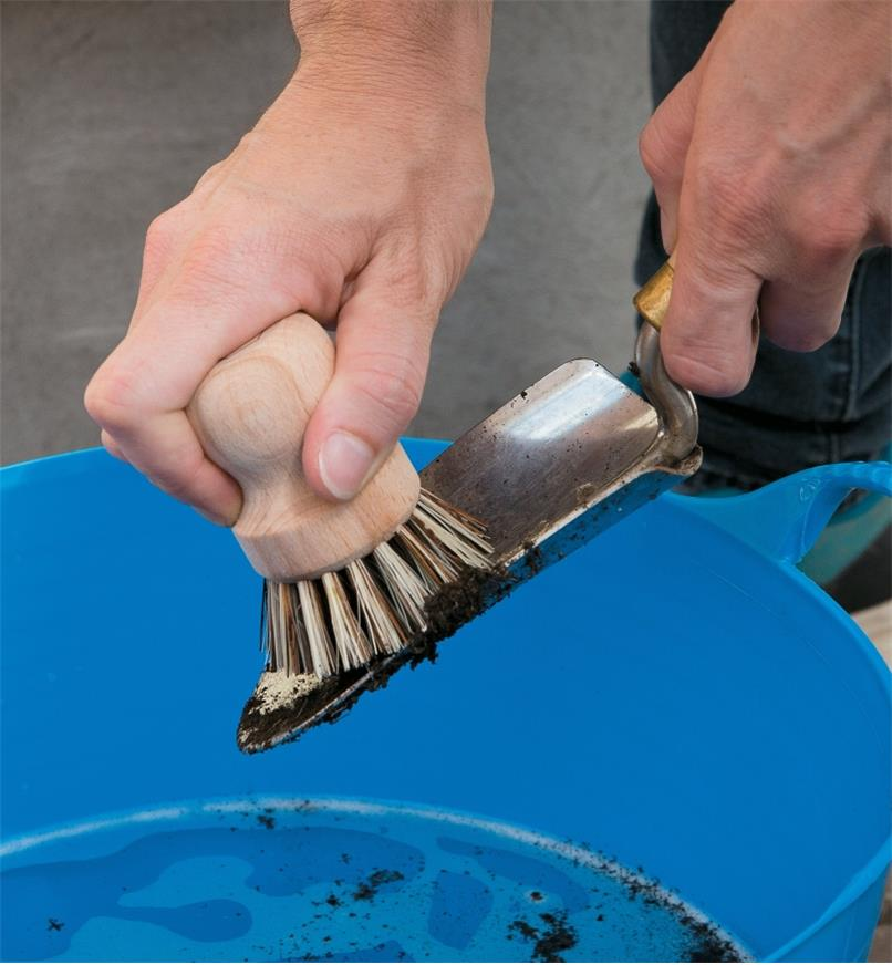 Using the scouring brush to clean a trowel