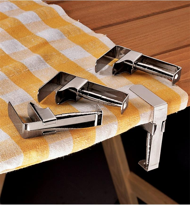 One tablecloth clip holding a tablecloth on a picnic table, and three clips lying next to it