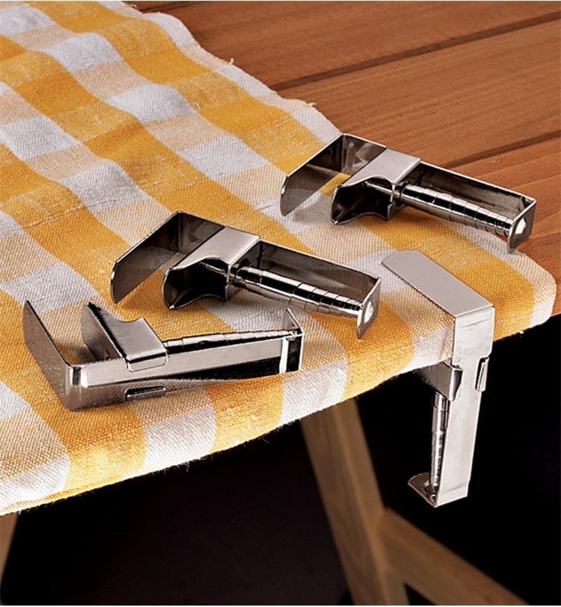 Une pince-nappe retenant une nappe sur une table à pique-nique et trois pince-nappe reposant sur la table