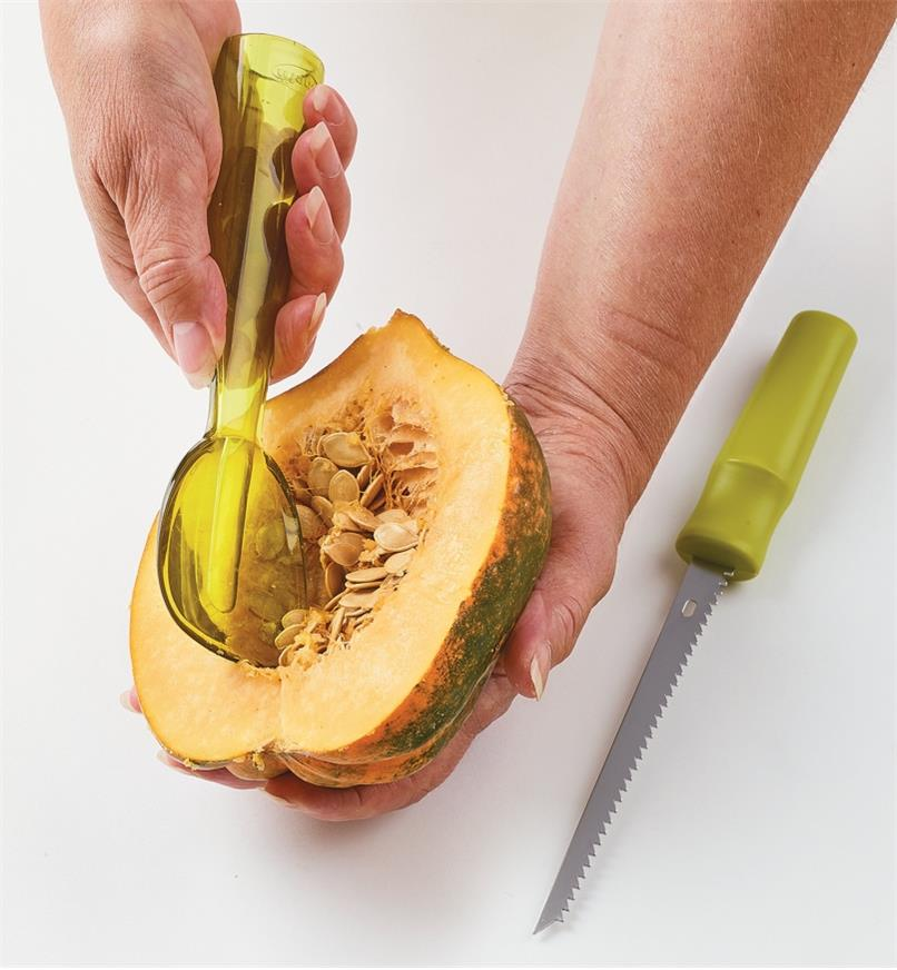 Using the scoop to remove seeds from an acorn squash