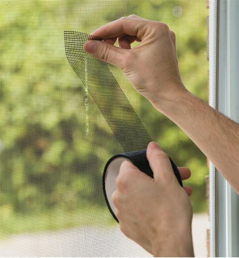 Using Screen Repair Tape to patch a tear in a window screen