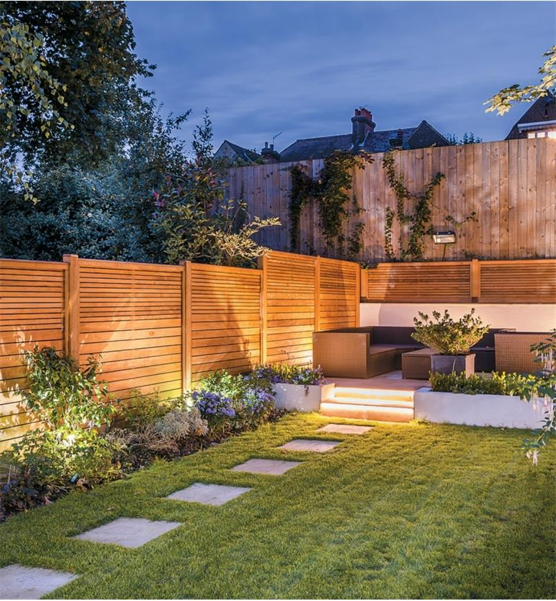 White Landscape Lights installed along a garden fence