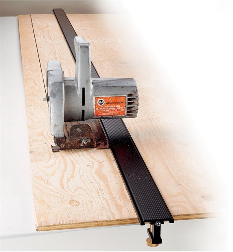 "100"" Power Tool Guide clamped to a sheet of plywood, guiding a circular saw"
