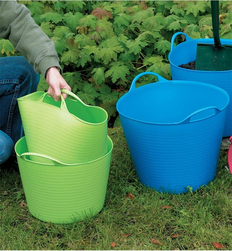 A woman lifts one tubtrug out of another tubtrug