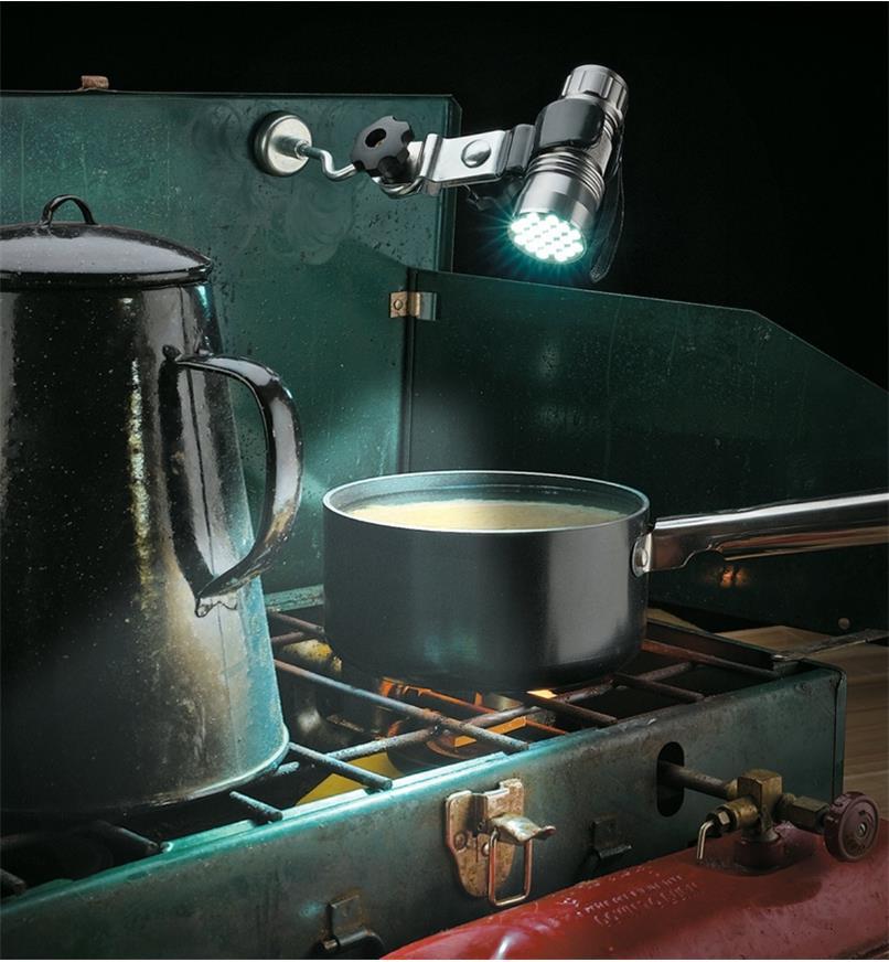 Flashlight holder affixing a flashlight to a camp stove lid to illuminate a pot on the burner