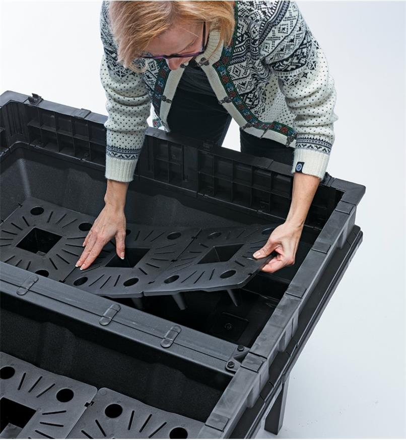 A woman places the slotted inserts in the Vegepod Container Garden