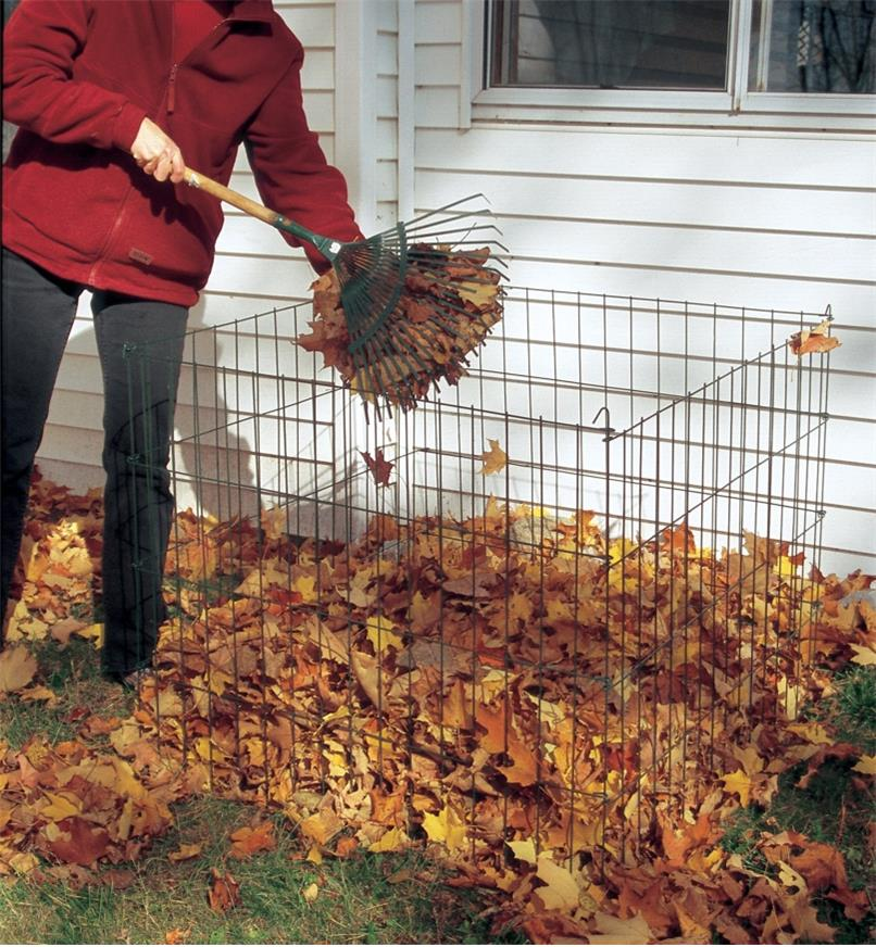 A woman forks leaves into a Wire Compost Bin