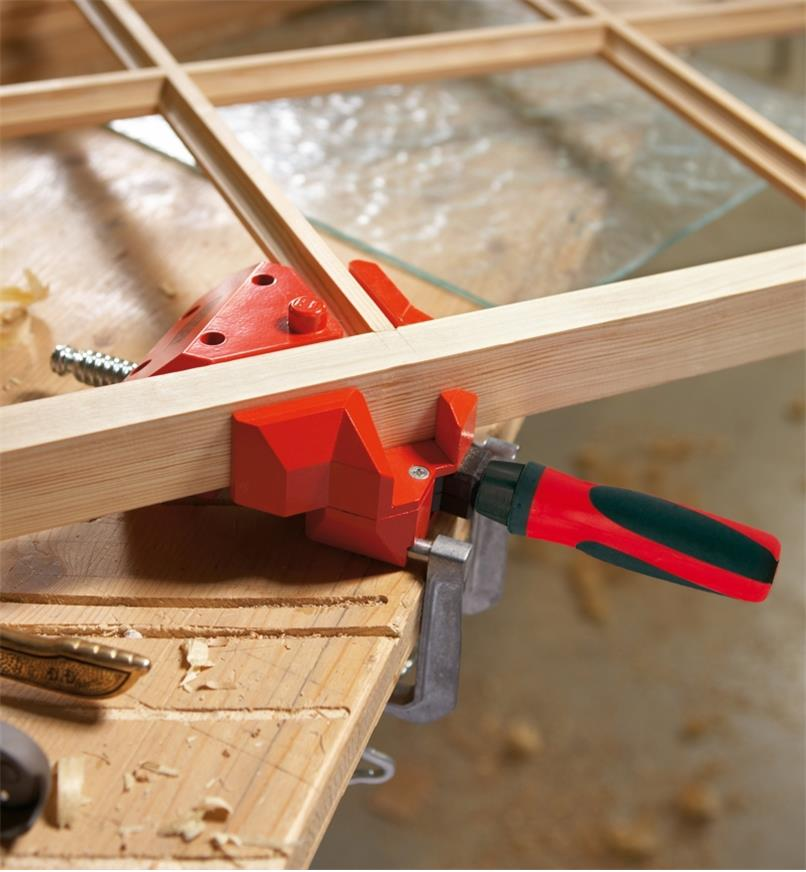 A Bessey small corner and T clamping fixture holding two pieces of a panel window frame at 90°