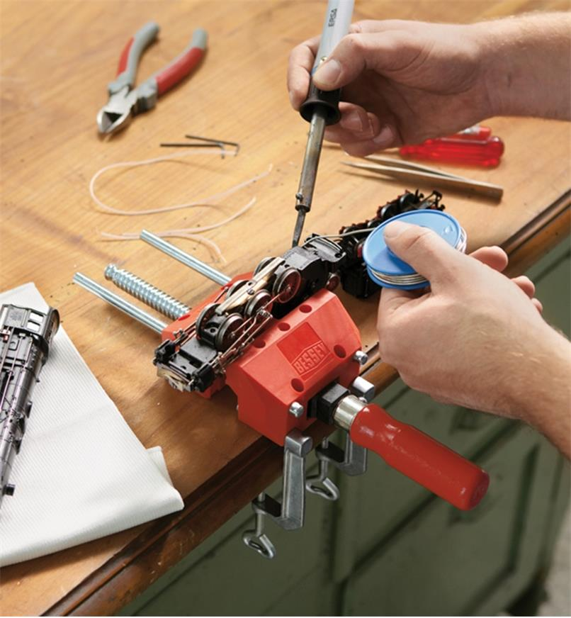 A Bessey portable hobby vise mounted to a table top, holding a model train being repaired