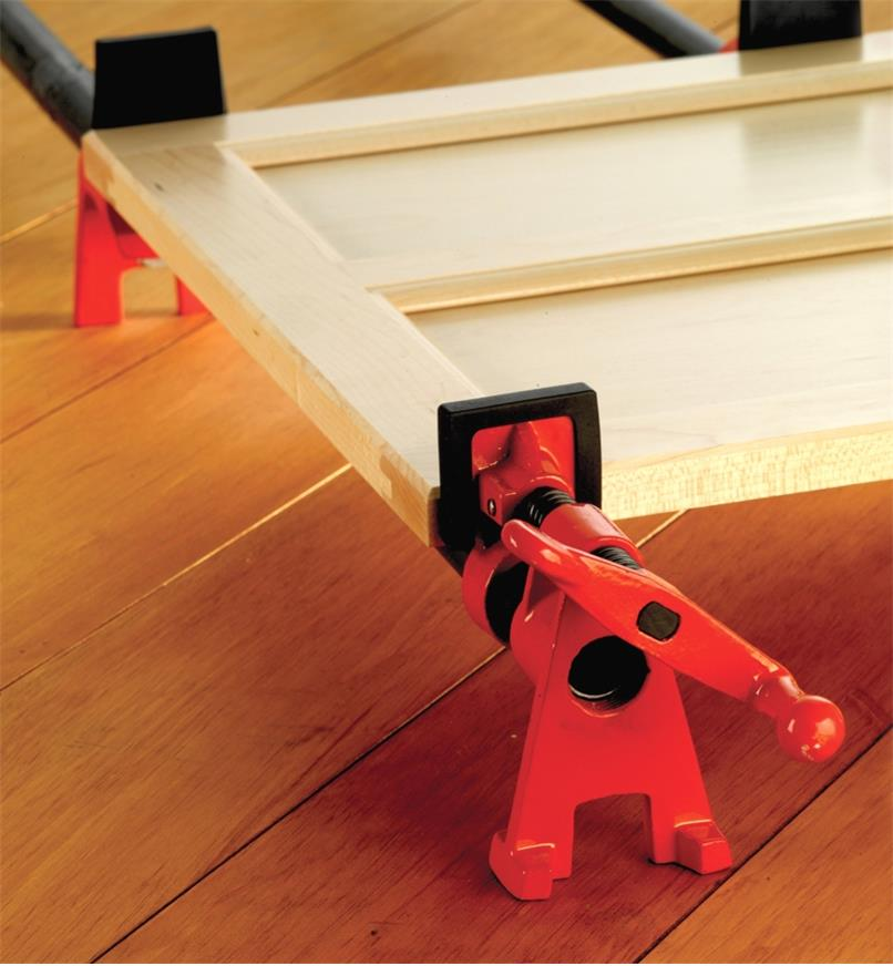 A cabinet door assembly held in a Bessey pipe clamp with Bessey pipe clamp pads mounted on the jaws
