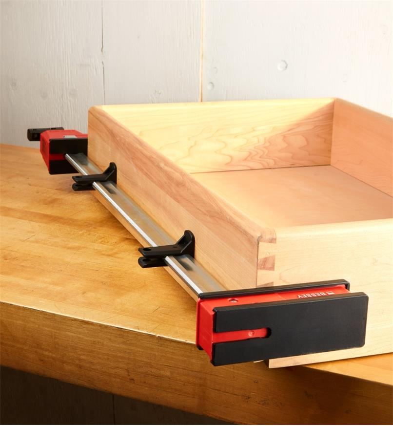 Two Bessey K-Body rail protectors mounted on the rail of K-Body clamp used to hold a drawer assembly
