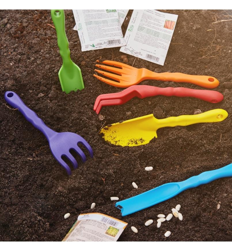 A set of six small garden tools shown in a garden bed with some seeds ready for planting