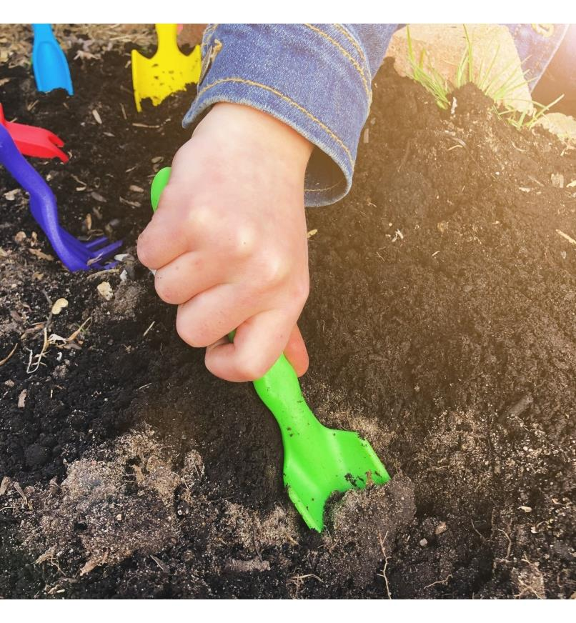 A child uses the narrow trowel from the Little Market Gardener Kit to dig in garden soil