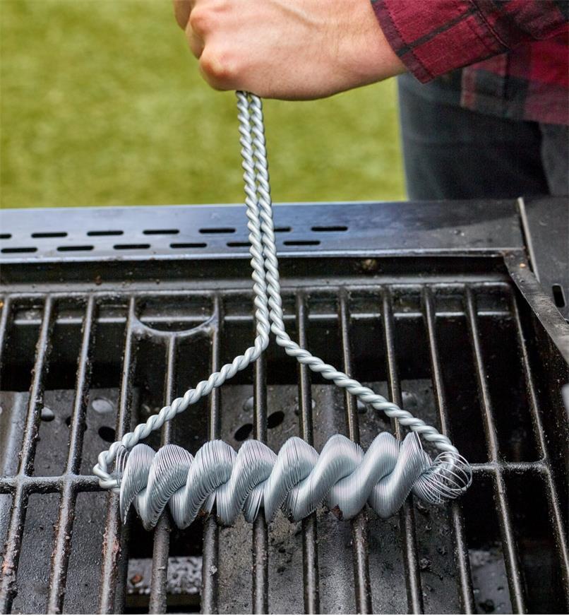 Gros plan de la tête de la brosse sans soies pour barbecue montrant les ressorts qui frottent le gril d'un barbecue