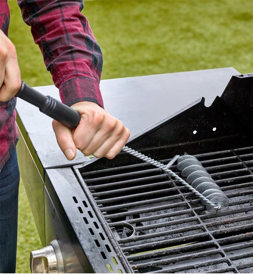 Homme nettoyant un gril avec une brosse sans soies pour barbecue
