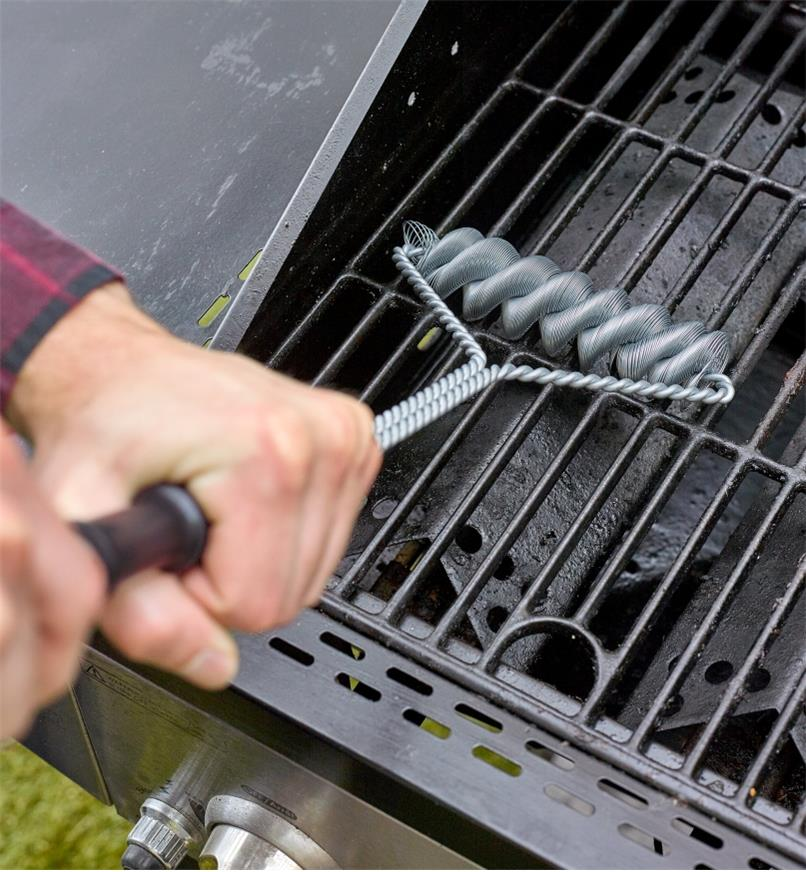A man using a two-handed grip on the barbecue brush handle to clean a grill