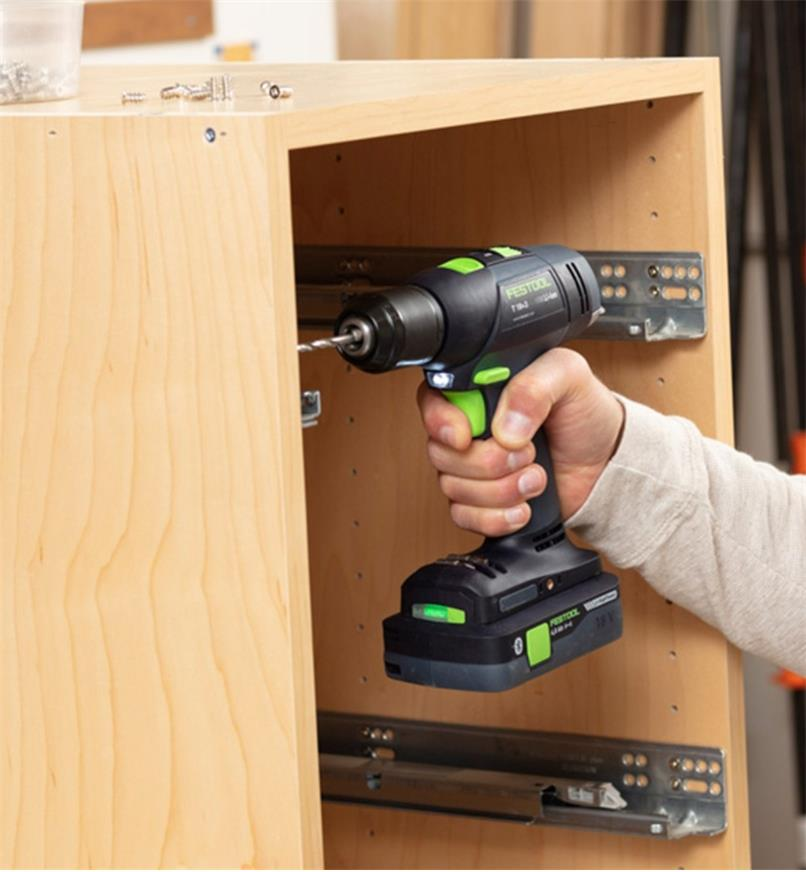 Installing hinges in a cabinet using the Festool T 18+3 Easy cordless drill equipped with the 4.0 Ah battery