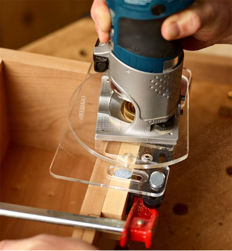 A woodworker uses a cabinet hinge template to guide a compact router when cutting a hinge mortise