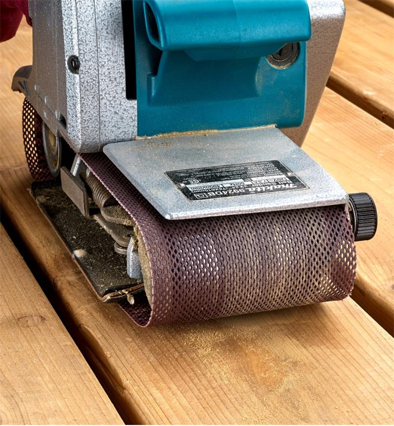 A Mirka Abranet belt on a belt sander being used to sand deck boards