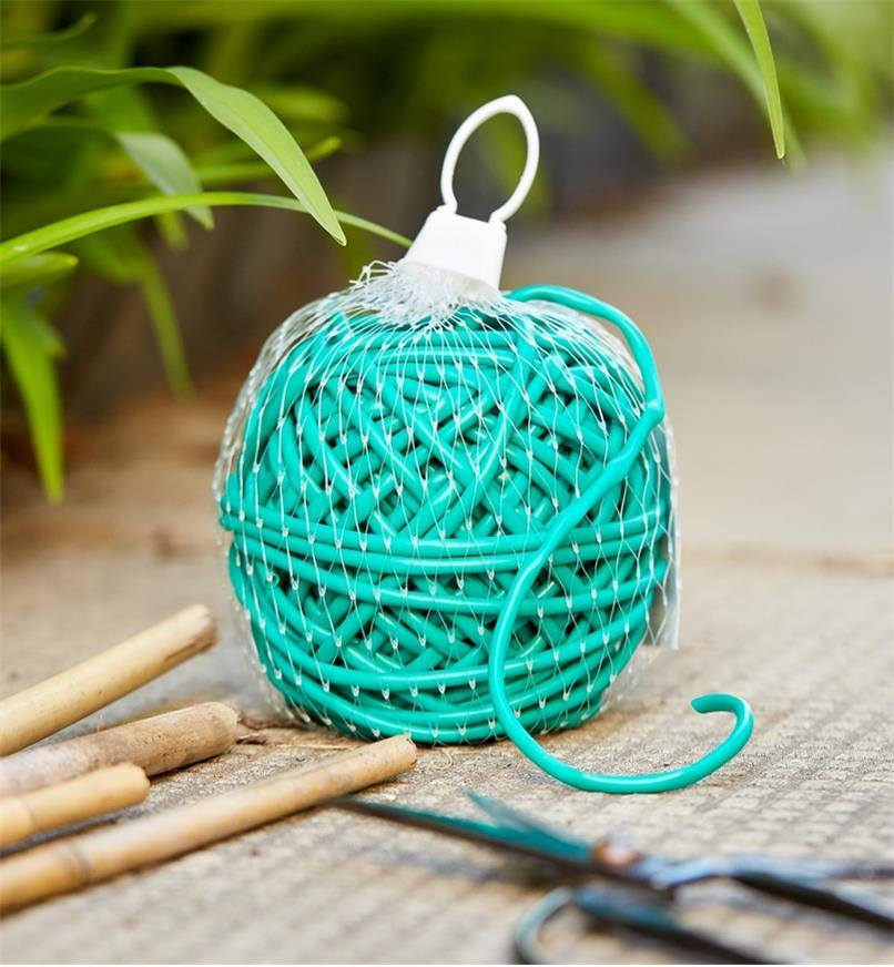 A 100' bundle of soft-stretch plant tie shown with bamboo garden stakes and a pair of scissors