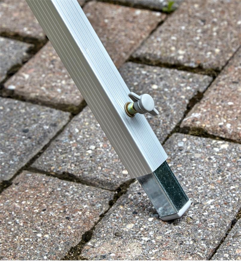 A close view of the folding aluminum table's levelling foot, used for stability on an uneven surface