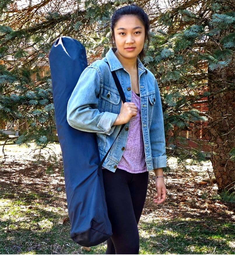 A woman carries a folding aluminum table contained in its nylon carrying case