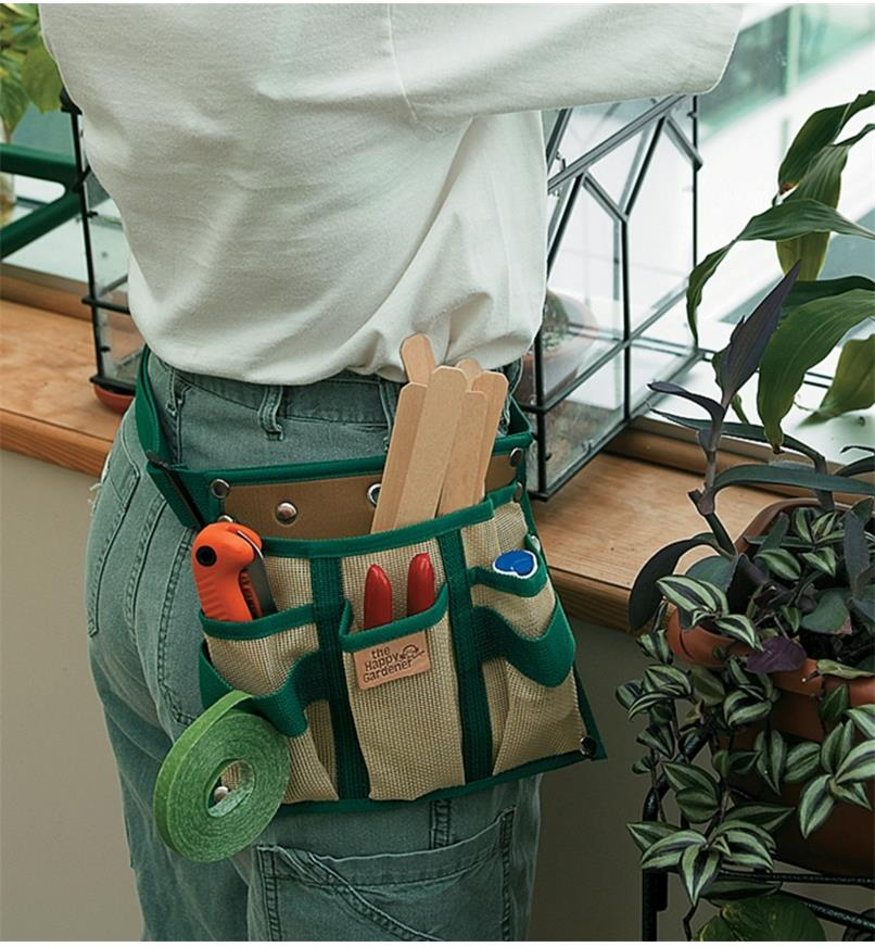 A woman wearing a 4-Pocket Tool Pouch and Belt in a greenhouse