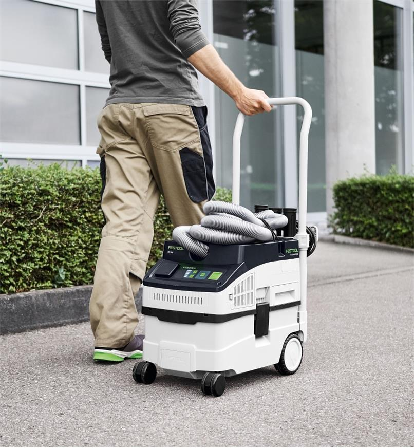 A person pulling a Festool dust extractor using the handle