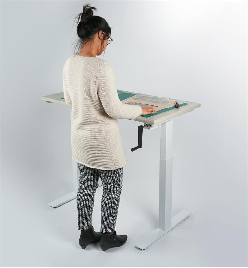 A woman standing works at a table made with the Manual Table Lift Kit