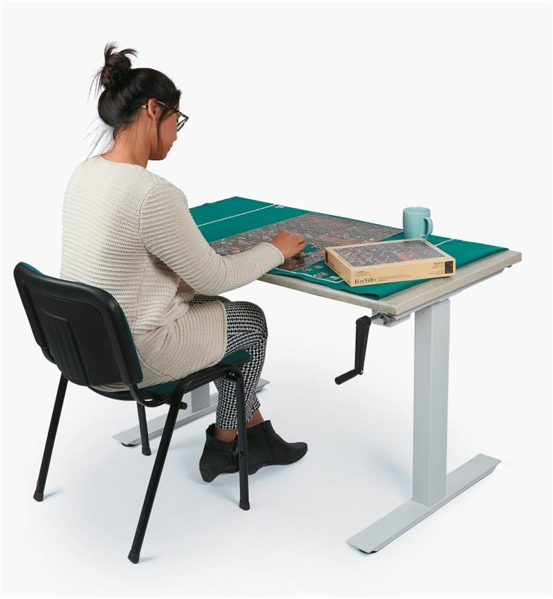 A woman sitting in a chair works on a jigsaw puzzle at a table made with the Manual Table Lift Kit