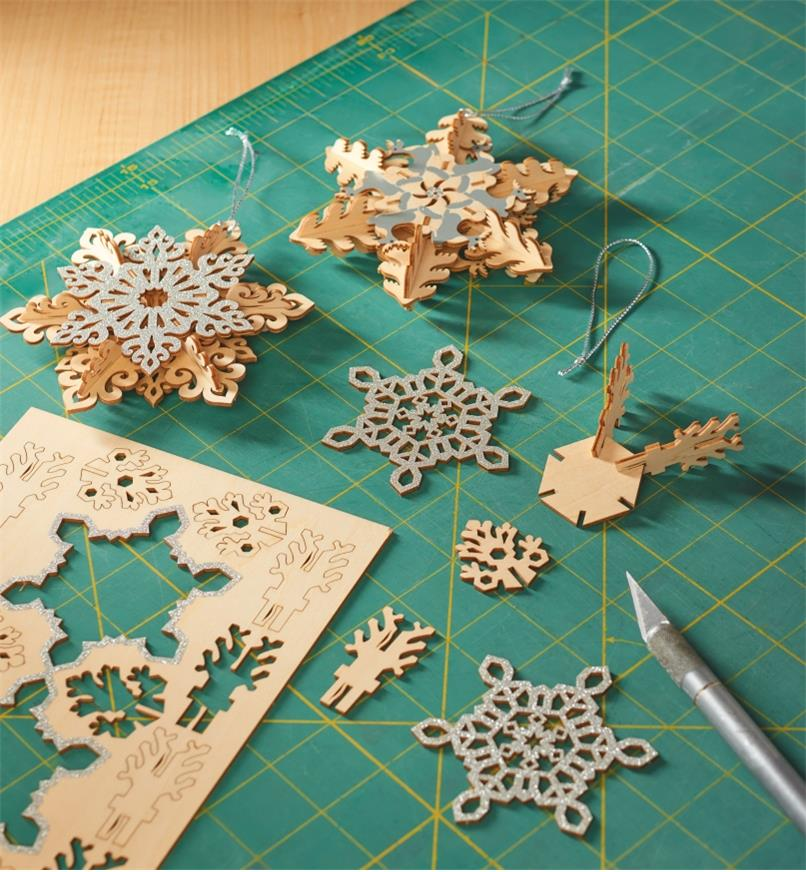 Two completed snowflake ornaments and one being made