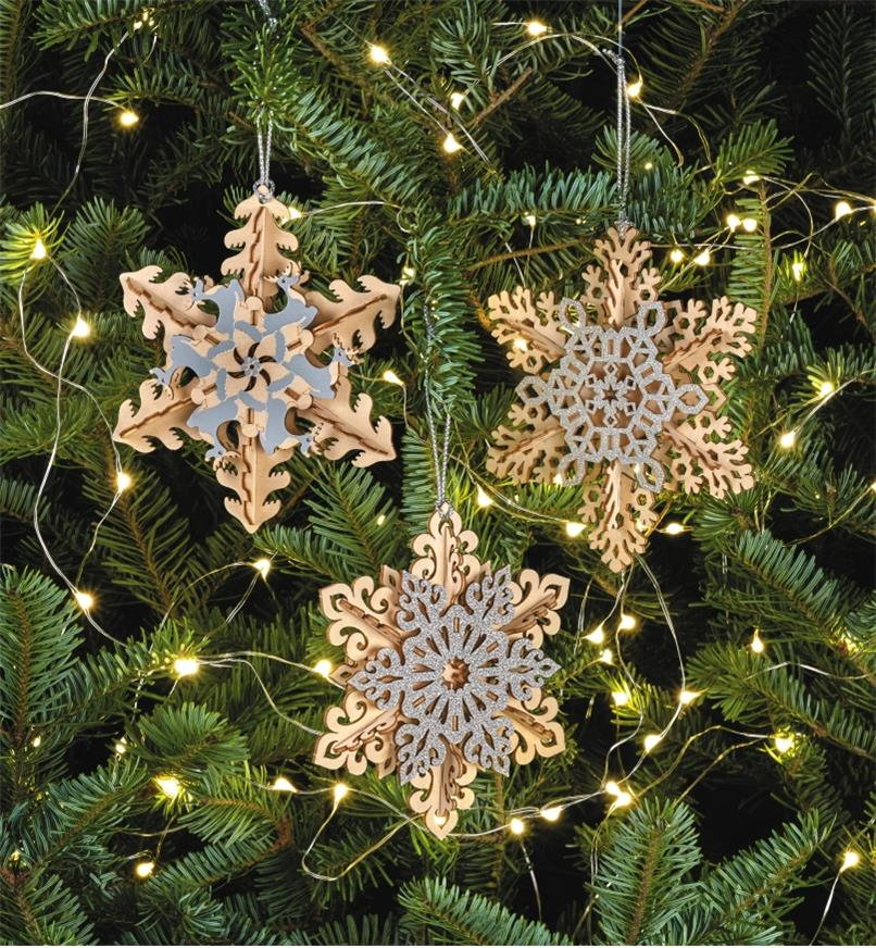 Three completed snowflake ornaments hanging on a Christmas tree