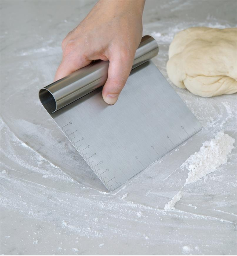 Bench Scraper used to collect flour on a countertop