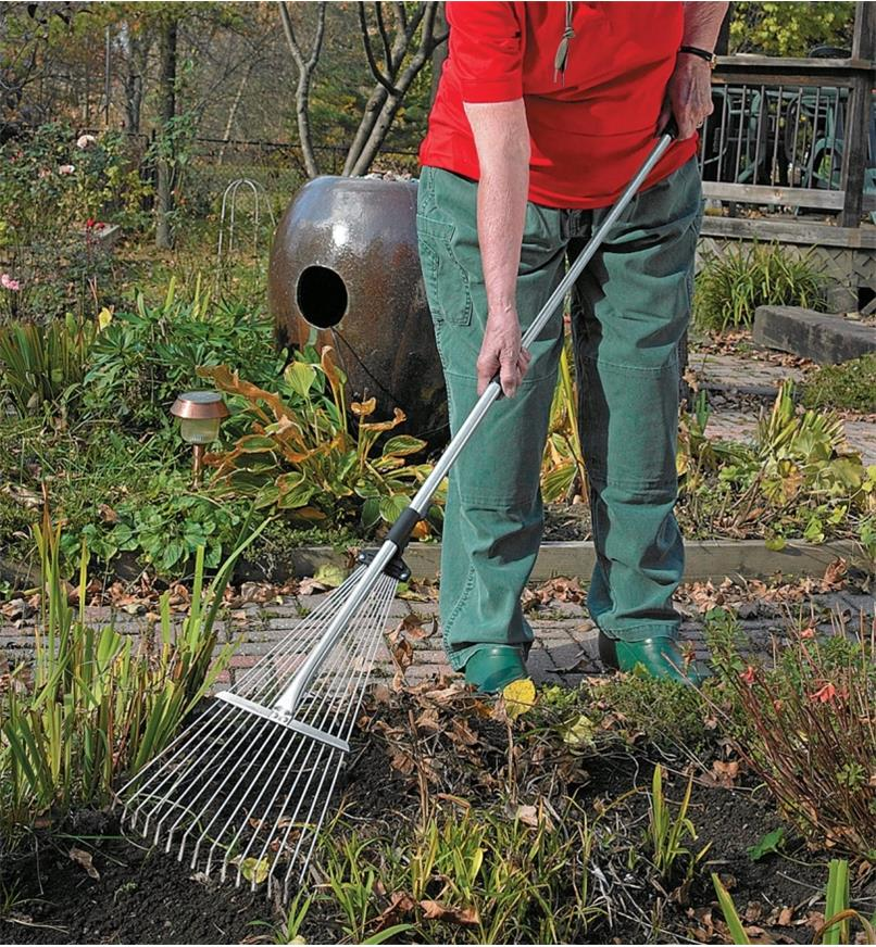 A woman rakes between garden plants using a Long-Handled Rake
