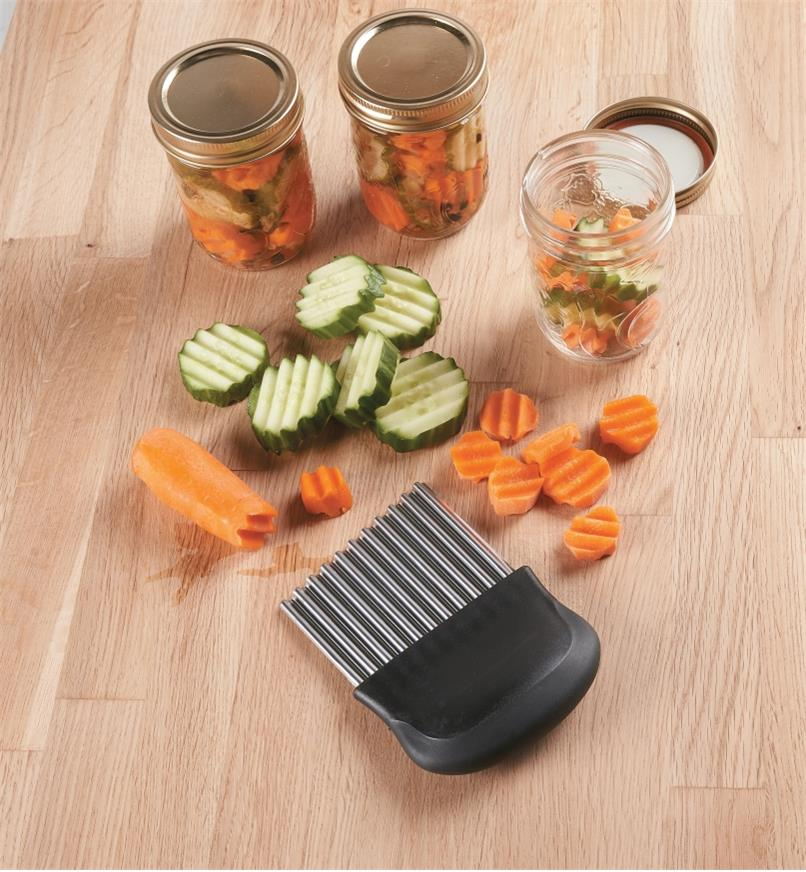 Carrot and cucumber being cut into crinkled slices for canning