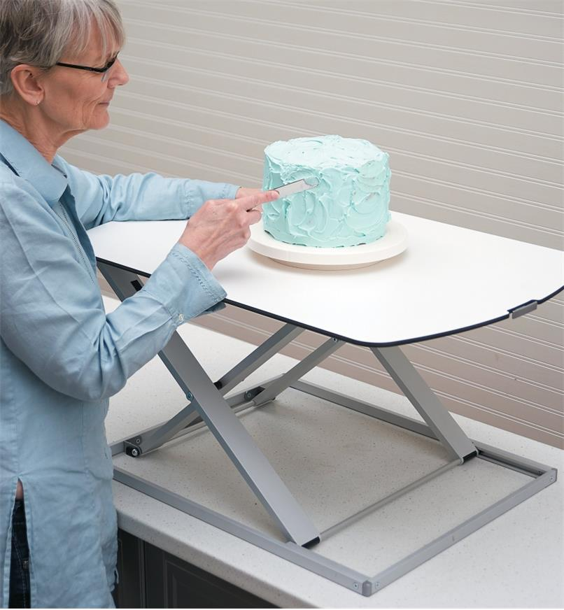 A woman frosts a cake on the Height-Adjustable Work Stand