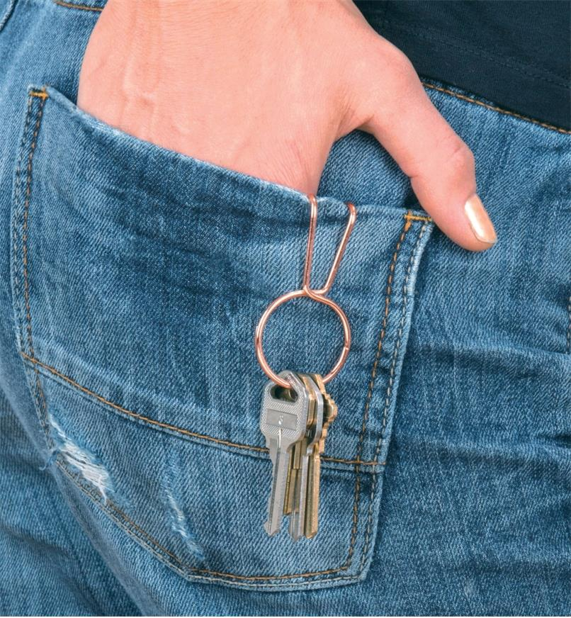 SqueezeRing Key Clip attached to a back pocket, with keys dangling