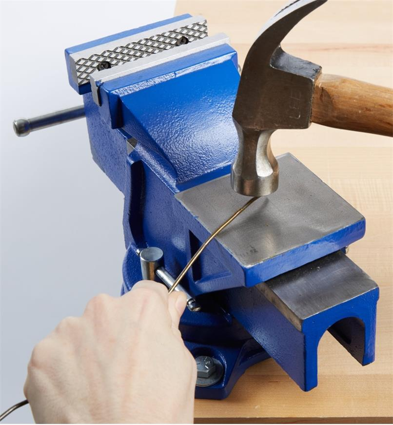 Bending a wire using a hammer against the anvil on the heavy-duty vise